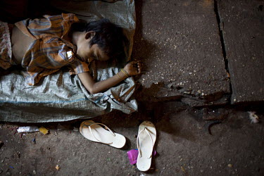 A young Burmese boy of Indian descent sleeps rough on the street in Yangon.
