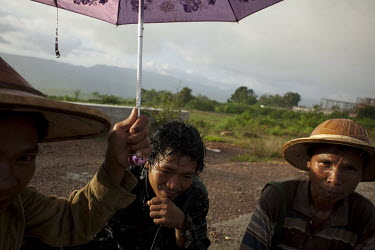 Construction workers sit in the rain at the new Yadana Cyber City near Mandalay.