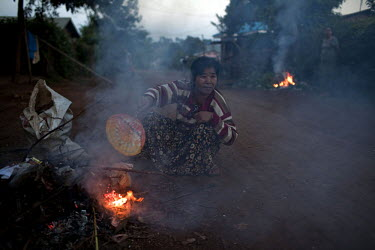 A woman burns leaves at dusk to keep mosquitoes away in Pyin U Lwin.
