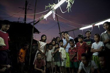 Children and adults congregate around a makeshift fairground game in the Hlaing Thaya slum district of Yangon.