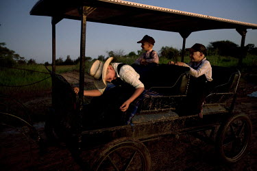 Boys travel on a horse drawn carriage, the only type of transportation allowed, in a Mennonite village. Near the city of Santa Cruz, there are about 15,000 Mennonites living in isolated communities. M...