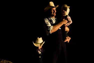 A child wearing a bonnet is held by its father on their farm in a Mennonite village. Near the city of Santa Cruz, there are about 15,000 Mennonites living in isolated communities. Mennonites are a gro...