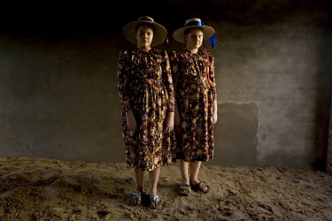 A portrait of two sisters in traditional dress outside their house in a Mennonite village. Near the city of Santa Cruz, there are about 15,000 Mennonites living in isolated communities. Mennonites are...