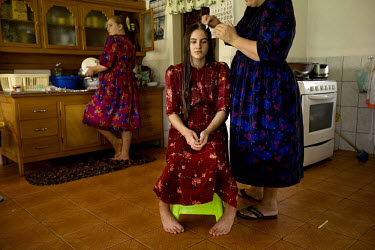 A girl has her hair braided by her mother at their home in a Mennonite village. Near the city of Santa Cruz, there are about 15,000 Mennonites living in isolated communities. Mennonites are a group of...
