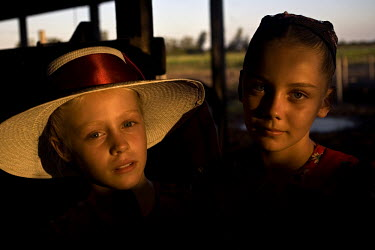 A portrait of two sisters outside their house in a Mennonite village. Near the city of Santa Cruz, there are about 15,000 Mennonites living in isolated communities. Mennonites are a group of Christian...