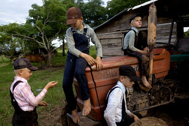 Children play on a tractor in a Mennonite village. Near the city of Santa Cruz, there are about 15,000 Mennonites living in isolated communities. Mennonites are a group of Christian Anabaptists, part...