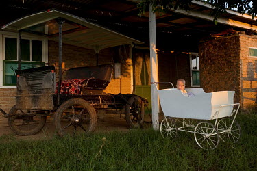 A baby sits in an old-fashioned pram next to a larger carriage outside a house in a Mennonite village. Near the city of Santa Cruz, there are about 15,000 Mennonites living in isolated communities. Me...
