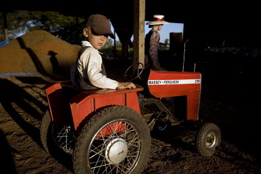 A boy plays on a toy Massey-Ferguson tractor on a farm in a Mennonite village. Near the city of Santa Cruz, there are about 15,000 Mennonites living in isolated communities. Mennonites are a group of...