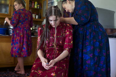 A mother braids her daughter's hair at their home in a Mennonite village. Near the city of Santa Cruz, there are about 15,000 Mennonites living in isolated communities. Mennonites are a group of Chris...