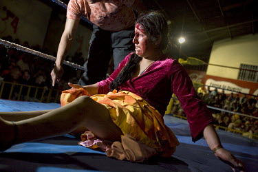 17 year old wrestler Alicia Flores (fighting name), Patricia Kaly (real name) on the ground during a fight at the Multifuncional building in El Alto. Patricia is a Cholita, a wrestler of native Aymara...