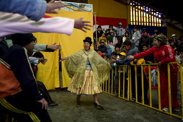 26 year old wrestler Juanita la Carinosa (fighting name), Mery Llanos Saenz (real name) encourages the crowd as she enters the fighting area at the Multifuncional building in El Alto. Mery is a Cholit...