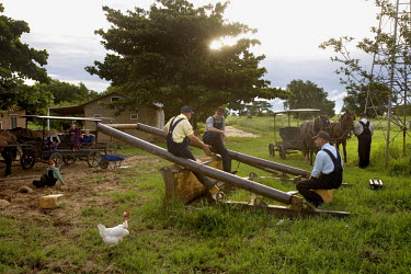 Men sit on an old piece of farming equipment near horse drawn carriages in a Mennonite village. Near the city of Santa Cruz, there are about 15,000 Mennonites living in isolated communities. Mennonite...