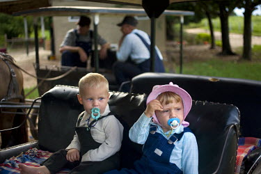Two children suck their dummies as they sit in a horse drawn carriage, the only type of transportation allowed, in a Mennonite village. Near the city of Santa Cruz, there are about 15,000 Mennonites l...