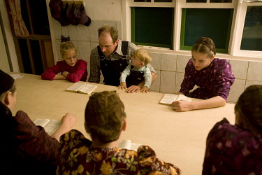 The Rempel family sing religious songs around a table at their home in a Mennonite village. Near the city of Santa Cruz, there are about 15,000 Mennonites living in isolated communities. Mennonites ar...