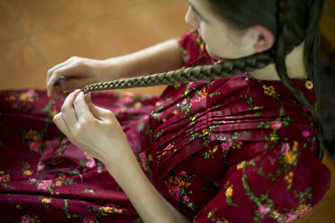 A girl braids her hair at her home in a Mennonite village. Near the city of Santa Cruz, there are about 15,000 Mennonites living in isolated communities. Mennonites are a group of Christian Anabaptist...