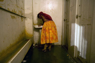 17 year old wrestler Alicia Flores (fighting name), Patricia Kaly (real name) leans over a sink in a bathroom after a fight at the Multifuncional building in El Alto. Patricia is a Cholita, a wrestler...
