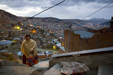 26 year old wrestler Yolanda La Amorosa (fighting name), Veraluz Cortez (real name) walks up steps in her neighbourhood overlooking La Paz. Veraluz is a Cholita, a wrestler of native Aymara descent. W...