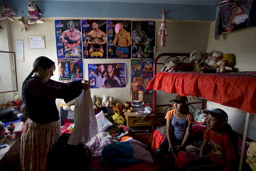 29 year old wrestler Martha La Altena (fighting name), Yenny Wilma Maraz (real name) stands in her daughters' room, with posters of famous wrestlers on the wall. Yenny is a Cholita, a wrestler of nati...