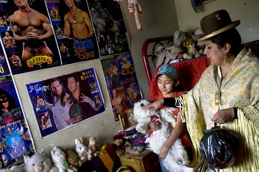 29 year old wrestler Martha La Altena (fighting name), Yenny Wilma Maraz (real name) stands in her daughters' room playing with their dog, with posters of famous wrestlers on the wall. Yenny is a Chol...