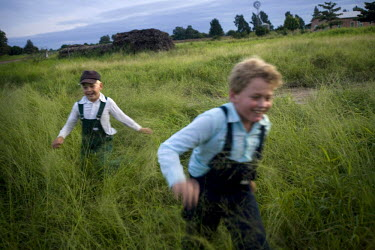 Two brothers run through a field in a Mennonite village. Near the city of Santa Cruz, there are about 15,000 Mennonites living in isolated communities. Mennonites are a group of Christian Anabaptists,...