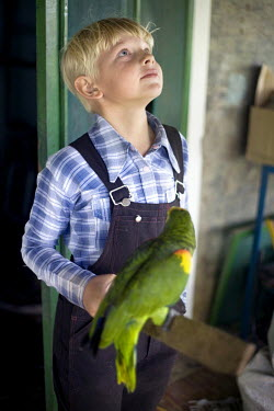 A boy stands by his family's parrot in a Mennonite village. Near the city of Santa Cruz, there are about 15,000 Mennonites living in isolated communities. Mennonites are a group of Christian Anabaptis...