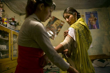 17 year old wrestler Alicia Flores (fighting name), Patricia Kaly (real name) has her injured arm wrapped up by her sister Marina Kaly in her room. Patricia is a Cholita, a wrestler of native Aymara d...