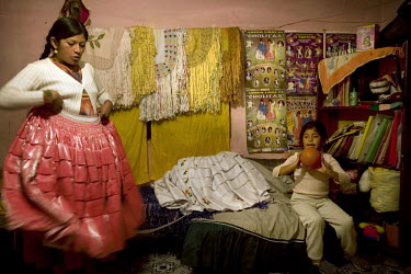 26 year old wrestler Yolanda La Amorosa (fighting name), Veraluz Cortez (real name), left, folds polleras (traditional dresses) in her room with her daughter. Veraluz is a Cholita, a wrestler of nativ...
