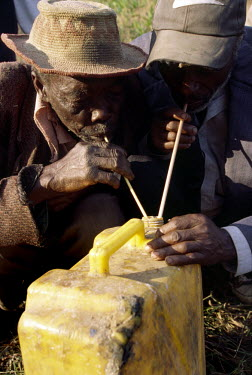 Two men settle their differences by symbolically drinking palm wine from the same container at a counsel of the Bashingantahe (roughly meaning wise men). The Bashingantahe, a traditional local court s...