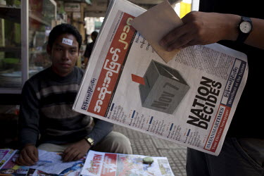 A newspaper vendor sits with a sticker attached to his face that reads iVote, while a customer reads an election special newspaper for sale at a newsstand ahead of Burma's first multi-party elections...