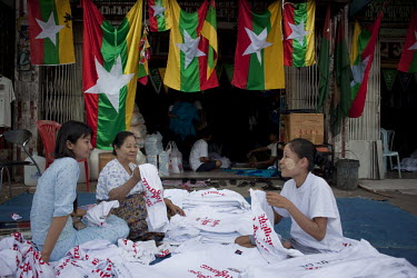 Staff fold T-shirts at a shop selling the new design Burmese flag in Rangoon (Yangon). The Burmese government have recently introduced a new Burmese flag as part of the 2010 election process.