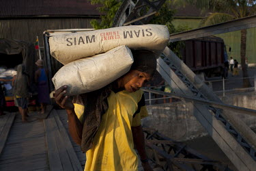 A dock labourer loads sacks of Siam brand cement onto a boat at the Rangoon (Yangon) river docks.