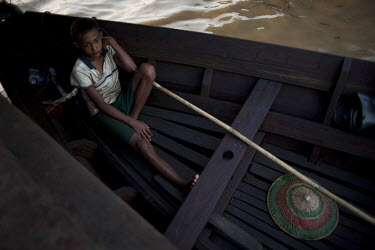 A boy sits in a boat at the docks in Rangoon (Yangon).