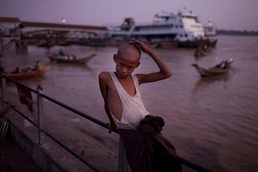 A young boy sits on a railing next to the Rangoon (Yangon) River docks. In the background a passenger ferry is moored on at a jetty.