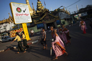 Buddhist nuns pass an election poster, near a temple, for the government-backed USDP (Union Solidarity and Development Party) in the old capital Rangoon (Yangon) prior to Burma's first multi-party ele...