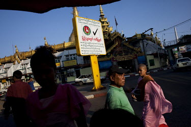 People pass an election poster, near a Buddhist temple, for the government-backed USDP (Union Solidarity and Development Party) in the old capital Rangoon (Yangon) prior to Burma's first multi-party e...
