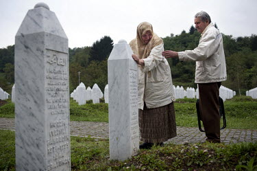 Rabija (left) and Munib Hodzic at the graveside of their only child Sabahudin buried at the cemetery for the victims of the Srebrenica massacre in Potocari. Sabahudin was one of 8,000 mainly Bosnian M...