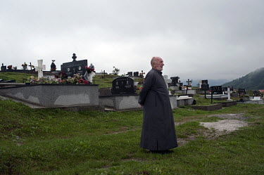 Vojislav Carkic, a priest and Major in the army of Republika Srpska, walks to the graves of Ratko Mladic's mother, father and brother in the village of Donje Miljevici. Former Bosnian Serb general Rat...