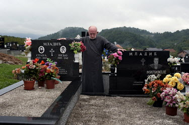 Vojislav Carkic, a priest and Major in the army of Republika Srpska, stands over the graves of Ratko Mladic's mother, father and brother in the village of Donje Miljevici. Former Bosnian Serb general...