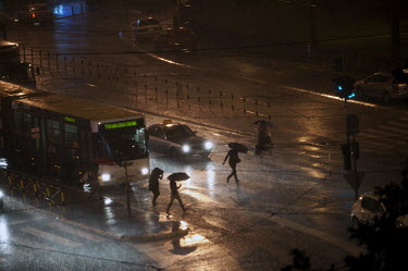 Pedestrians running across a road, through the rain, in central Belgrade.