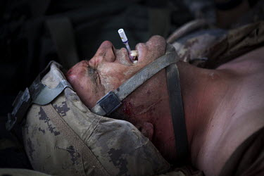 A wounded Canadian soldier winces in pain as he is treated by US Army medics from Charlie Company, Sixth Battalion, 101st Aviation Regiment on board a medevac helicopter near Kandahar. He was wounded...