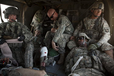 Four US Army soldiers from the 101st Airborne are treated by a medic on board a medevac helicopter from Charlie Company, Sixth Battalion, 101st Aviation Regiment near Kandahar, after their convey was...