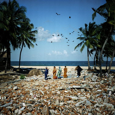 A group of women walk among the brick rubble of a destroyed house soon after the 2004 Tsunami.