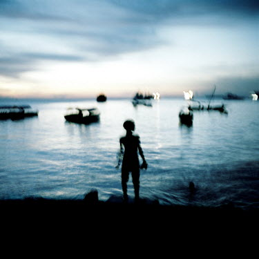 A boy stands on the seashore with boats moored.