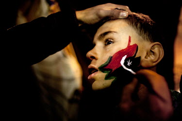 A boy has the pre Gaddafi Libyan flag painted onto his face at the rebels' headquarters in Benghazi. Benghazi is now in the hands of the rebels. On 17 February 2011 Libya saw the beginnings of a revol...