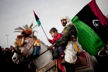 A man and child ride on a horse with a pre Gaddafi Libyan flag as 'The army of rebel volunteers' march through the streets of Benghazi. These young men who have no military background have undergone f...