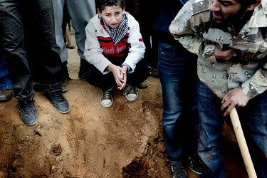 A child mourns at a mass funeral for approximately 20 people who died on the evening of March 4, when a huge deposit of ammunition exploded outside of Benghazi. Rebels claim that it was Gaddafi's forc...