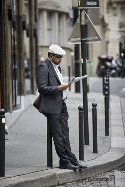 A man reads a newspaper on Rue Mouffetard.
