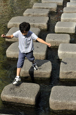 A young boy crosses the formerly polluted river in Cheonggyecheon Stream Park which has recently been the focus of a masterful urban renewal project.