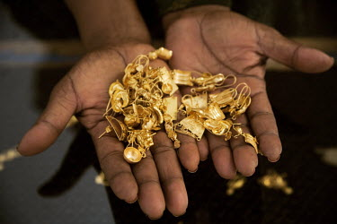 A woman selling gold from a stall in Hargeisa market holds out a handful of jewellery.
