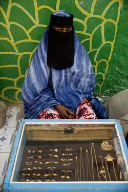 A woman selling gold from a stall in Hargeisa market sits behind a display case.